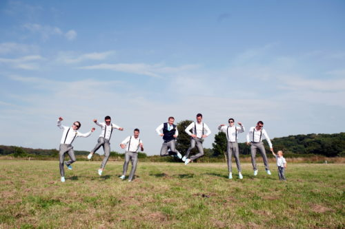 groom party jumping romantic couples shots in the roses at selden barns wedding venue west sussex