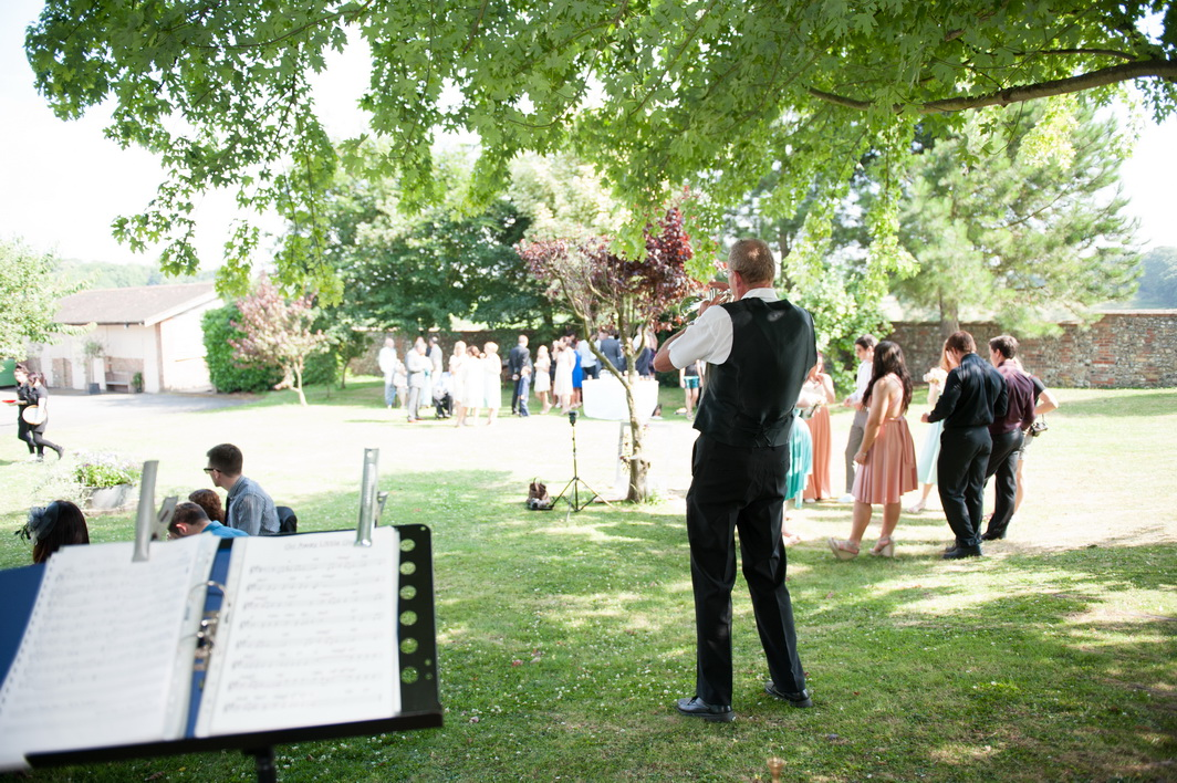 Jazz musician entertaining guests outside at a summer wedding at selden barns, worthing